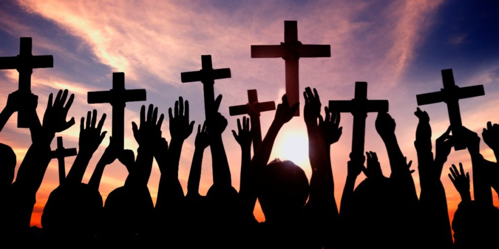 Silhouetted figures against a sunset holding crosses in the air.