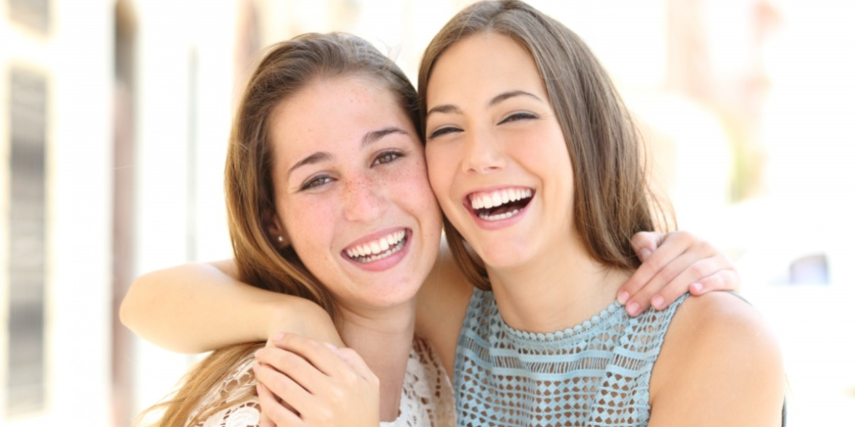 Two female friends hugging each other and smiling.